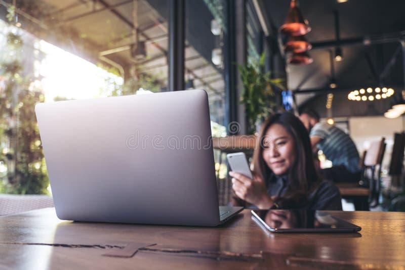 Imagem do close up de uma terra arrendada asiática bonita, de usar e de olhar da mulher de negócio o telefone esperto com o PC do imagens de stock royalty free