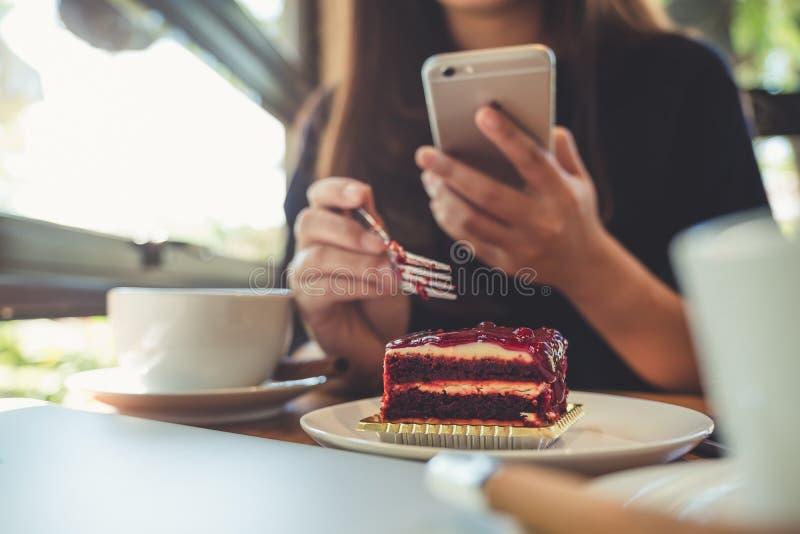 Imagem do close up de uma terra arrendada, de usar e de olhar da mulher o telefone esperto ao comer um bolo com os copos e o port fotografia de stock