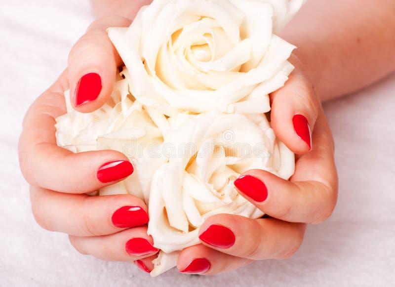 Imagem do close up do manicure vermelho com flores imagem de stock royalty free
