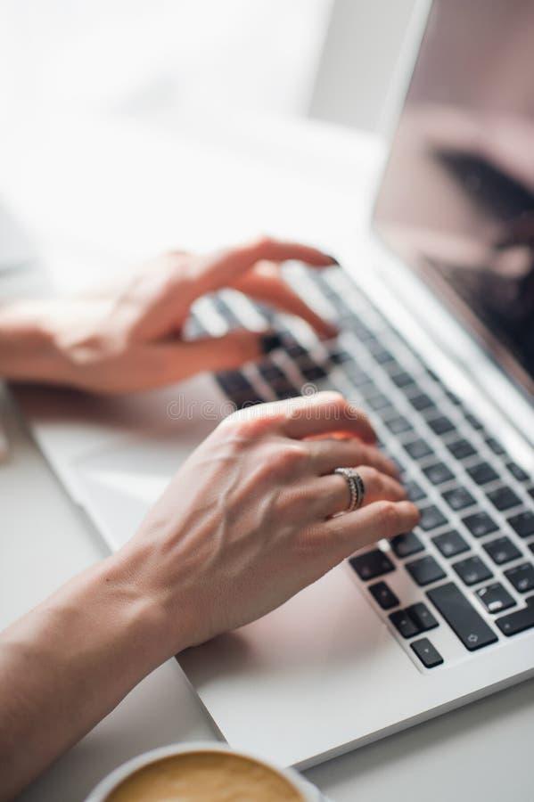 A imagem do close-up do ` s da mulher entrega a datilografia de uma mensagem em seu portátil durante o almoço imagens de stock royalty free