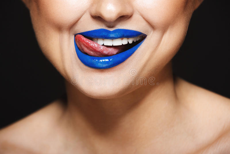 Imagem do close up do sorriso alegre do ` s da menina com batom azul Língua que lambe os bordos fotografia de stock royalty free