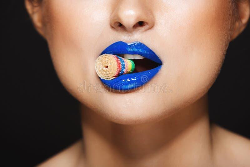 Imagem do close up dos bordos coloridos 'sexy' do ` s da mulher que guardam sweeties com dentes Sobre o fundo cinzento foto de stock royalty free