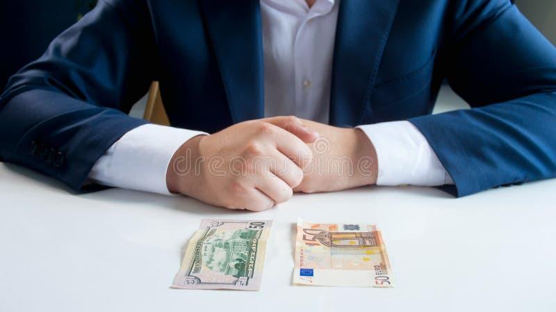 Imagem do close up do homem de negócios que duvida entre o investimento no euro ou o dinheiro do dólar fotos de stock royalty free