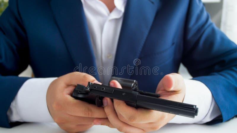 Imagem do close up do homem de negócios que senta-se atrás da mesa em seu escritório e que guarda o revólver imagem de stock