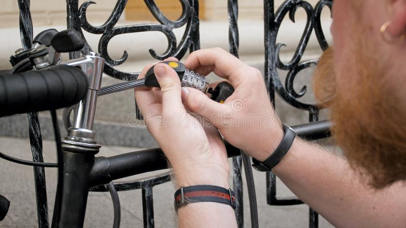 Imagem do close up do homem novo que trava o bicucle com fechamento de combinação foto de stock royalty free