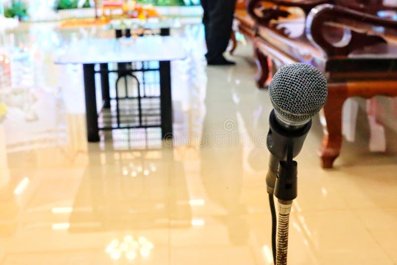 A imagem do close-up do microfone no suporte de aço borrou o fundo no evento imagem de stock