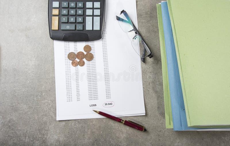 Imagem do conceito do lucro e da perda de uma pena, de uma calculadora e de umas moedas em originais financeiros imagens de stock