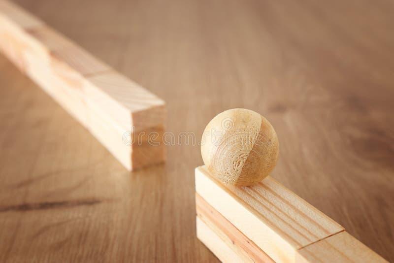 Imagem do conceito do negócio da educação e do desafio Bola de madeira na parede alta e necessidades de ser passado ao outro lado fotografia de stock