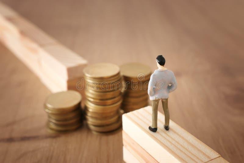 Imagem do conceito do negócio do desafio Um homem está na borda de uma diferença e olha uma pilha de moedas, pensando como ganhar imagens de stock royalty free