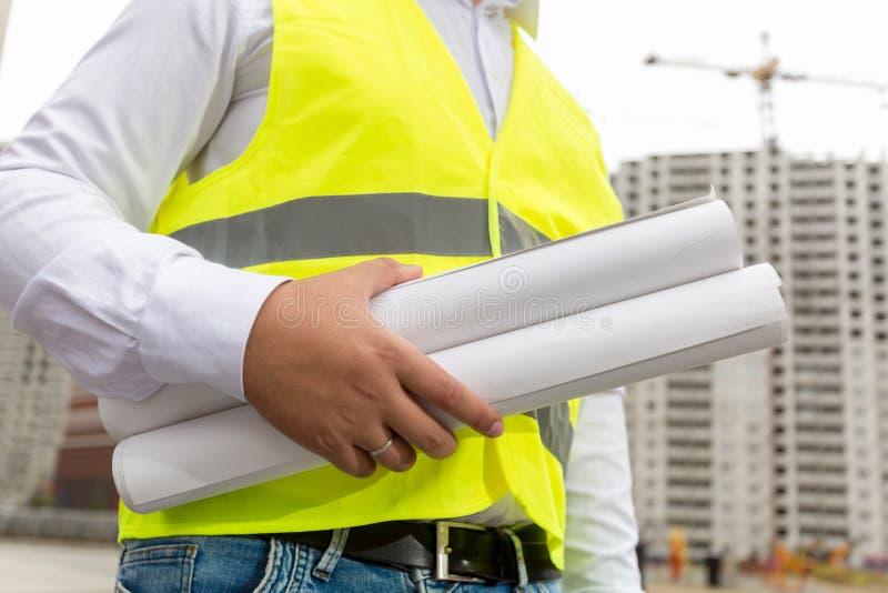 Imagem do coordenador de construção masculino com os modelos rolados em bu imagem de stock royalty free