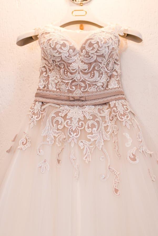 Imagem do corpete de um vestido de casamento bege em um gancho imagem de stock