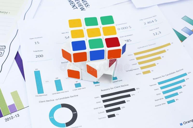 Imagem do cubo de Rubik no papel financeiro foto de stock royalty free
