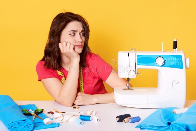 A imagem do desenhador de moda fêmea moreno atrativo houghtful, pensa sobre ideias novas ao sentar-se em seu lugar de trabalho is fotos de stock