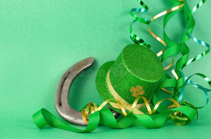 Imagem do dia de St Patrick do chapéu sparkly do duende do verde e do ouro e de uma ferradura da sorte com as ondas do verde e da imagens de stock