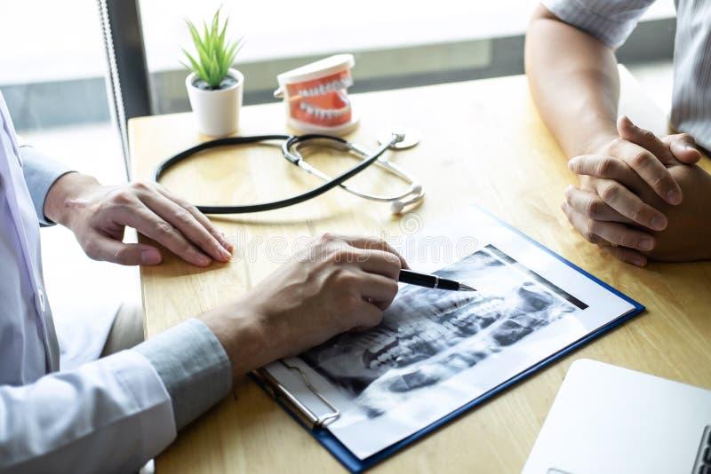 A imagem do doutor ou o dentista que apresenta com o filme de raio X do dente recomendam paciente no tratamento de dental e da od foto de stock