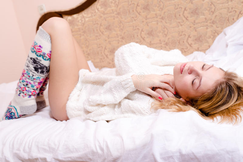 Imagem do encontro de relaxamento da mulher loura nova 'sexy' doce do encanto nela para trás na cama branca em uma camiseta e em  fotografia de stock