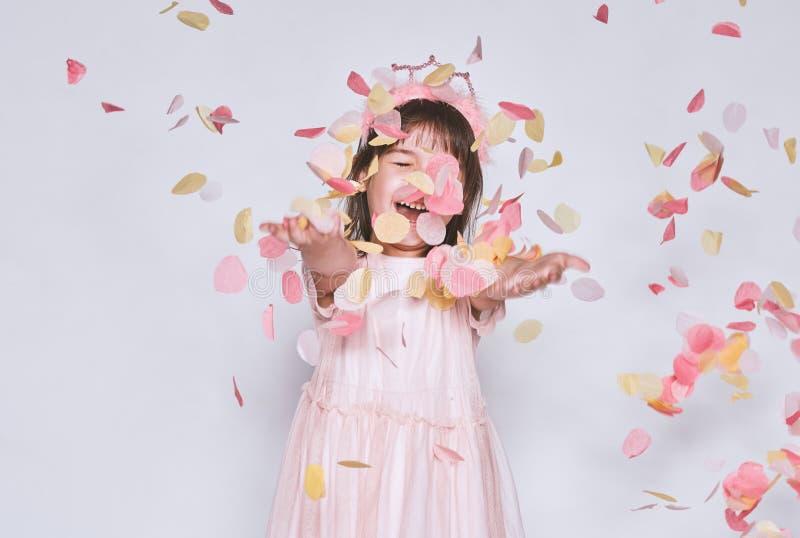 A imagem do estúdio da menina feliz que veste o vestido cor-de-rosa com a coroa da princesa na cabeça no fundo branco aprecia con fotografia de stock royalty free