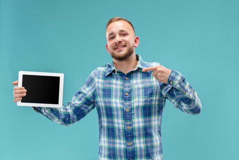 Imagem do estúdio do homem positivo isolada no fundo azul que está na roupa ocasional que guarda a tabuleta e que mostra a fotografia de stock