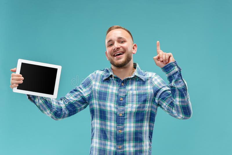 Imagem do estúdio do homem positivo isolada no fundo azul que está na roupa ocasional que guarda a tabuleta e que mostra a foto de stock