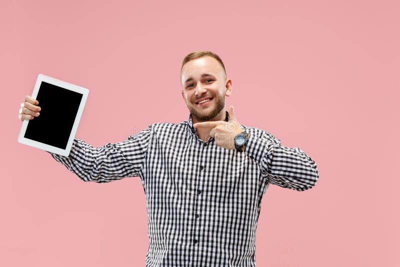 Imagem do estúdio do homem positivo isolada no fundo cor-de-rosa que está na roupa ocasional que guarda a tabuleta e que mostra a fotos de stock
