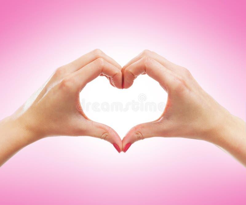 Imagem do Fim-acima das mãos fêmeas em uma forma de um coração imagens de stock