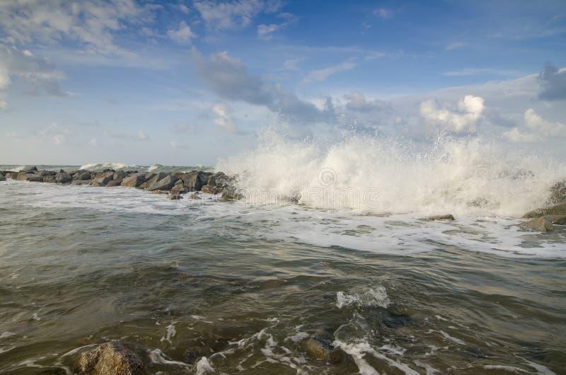 imagem do foco borrado e seletivo da onda que bate o quebra-mar imagem de stock