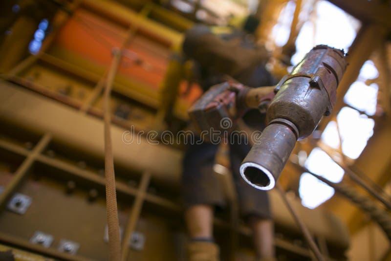 A imagem do grampeamento da arma do chocalho da bateria que conecta na segurança do chicote de fios poda com o trabalhador obscur imagem de stock