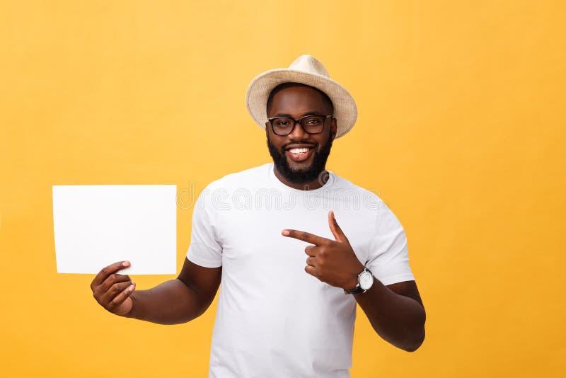 Imagem do homem afro-americano de sorriso novo que guarda a placa vazia branca e que aponta nela, no fundo amarelo, a cópia foto de stock royalty free