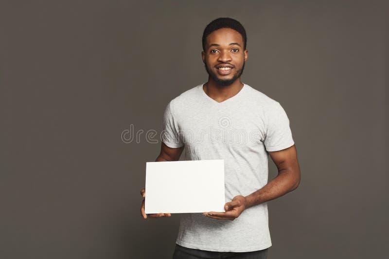 Imagem do homem afro-americano novo que guarda a placa vazia branca foto de stock