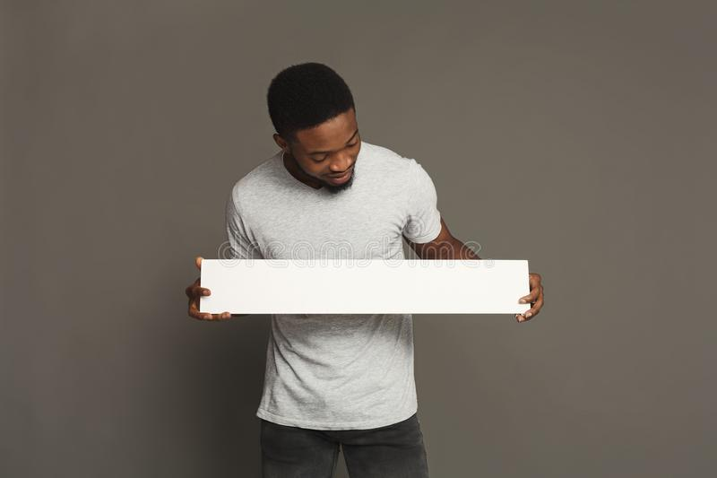 Imagem do homem afro-americano novo que guarda a placa vazia branca imagem de stock