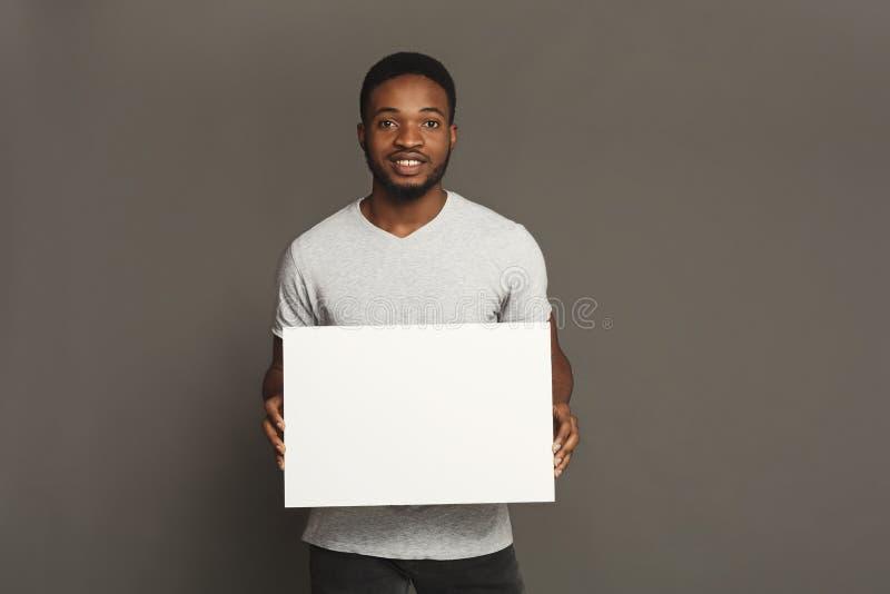 Imagem do homem afro-americano novo que guarda a placa vazia branca imagens de stock