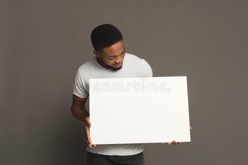 Imagem do homem afro-americano novo que guarda a placa vazia branca imagem de stock royalty free
