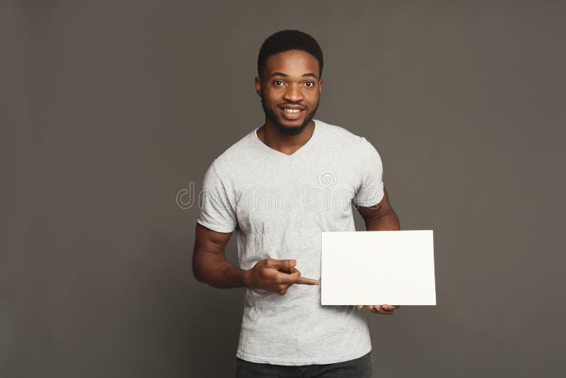 Imagem do homem afro-americano novo que guarda a placa vazia branca foto de stock royalty free