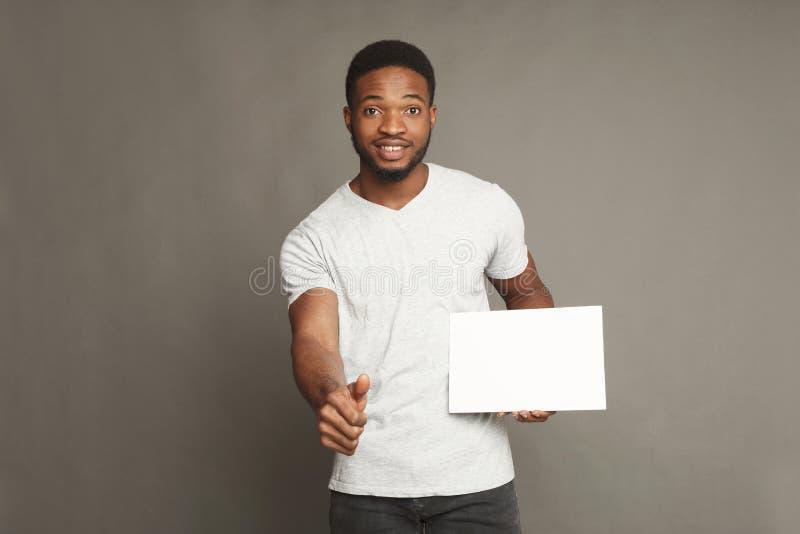 Imagem do homem afro-americano novo que guarda a placa vazia branca imagens de stock royalty free