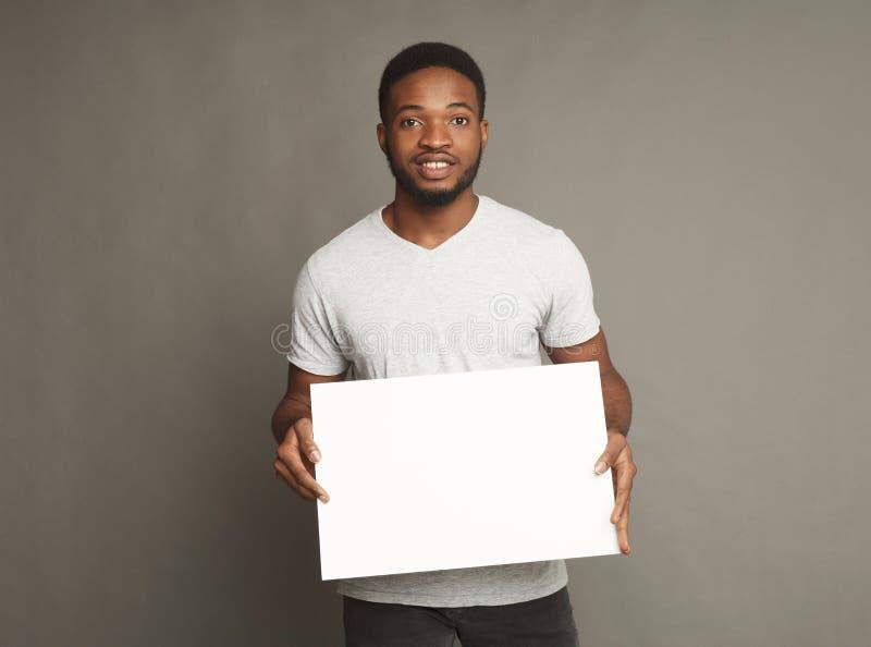 Imagem do homem afro-americano novo que guarda a placa vazia branca fotos de stock