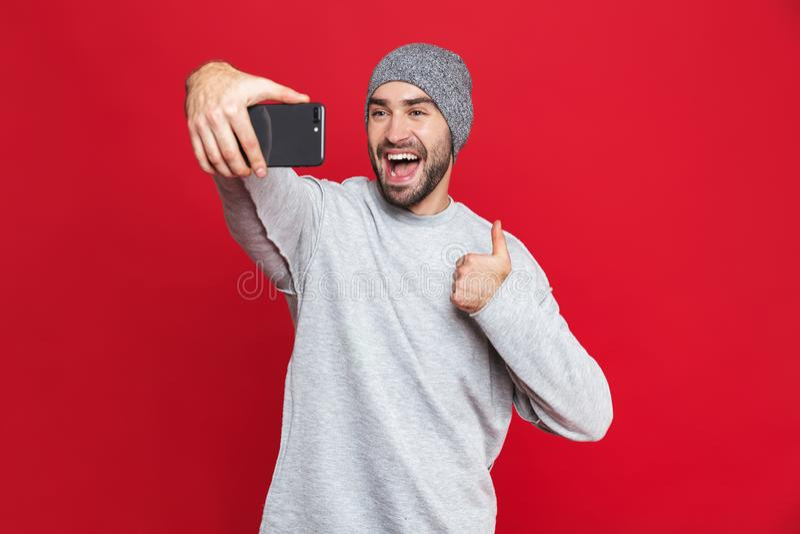 Imagem do homem caucasiano que ri ao tomar a foto do selfie no telefone celular isolado sobre o fundo vermelho imagens de stock