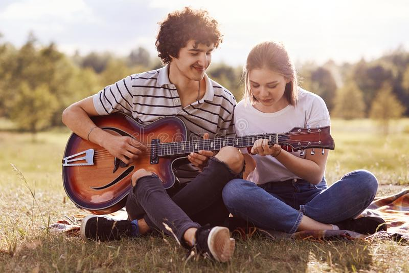 A imagem do homem consider?vel novo com cabelo encaracolado escuro ensina o jogo da guitarra seu amigo, par tem o piquenique no p fotografia de stock