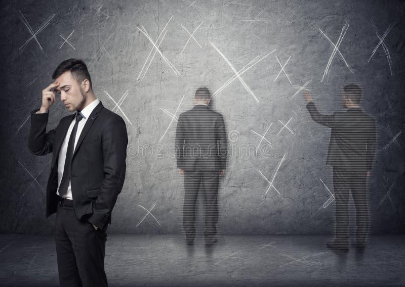 Imagem do homem de negócios que pensa sobre como resolver o problema com marcas 'de x' em torno dele fotografia de stock