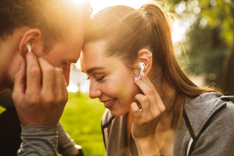 Imagem do homem dos jovens e da mulher felizes 20s nos fato de esporte, lis imagens de stock