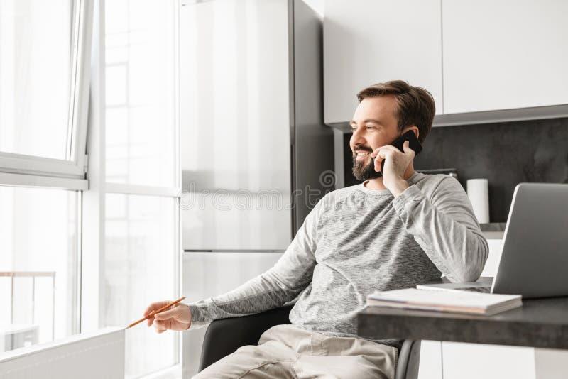Imagem do homem eficiente 30s que veste a roupa ocasional que trabalha sobre fotografia de stock