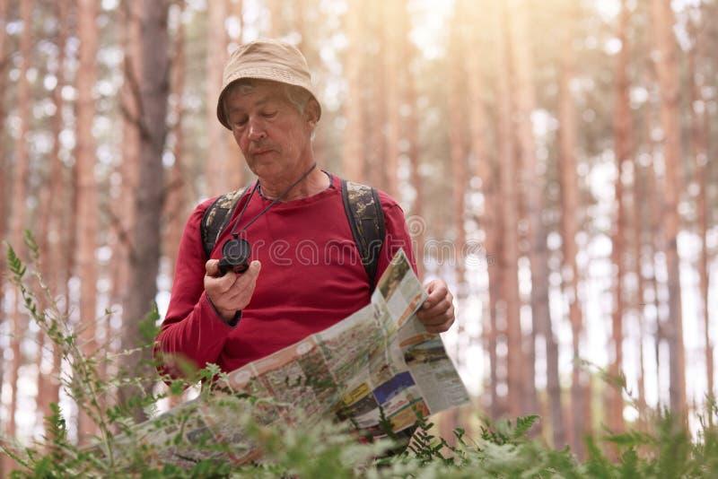 Imagem do homem do eldery que caminha e que olha o compasso e o mapa para o sentido para a viagem na floresta, equipamento ocasio fotos de stock