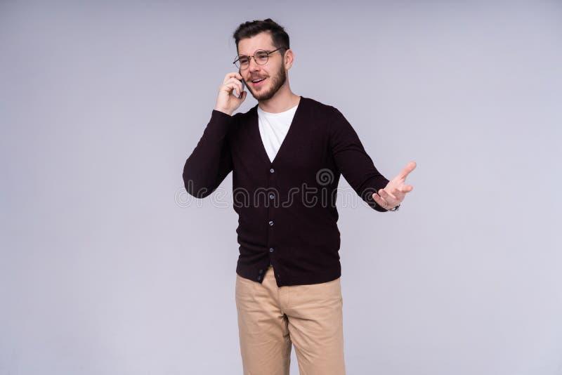 Imagem do homem emocional farpado novo feliz que está sobre o fundo branco da parede isolado Vista de lado ao falar perto fotografia de stock