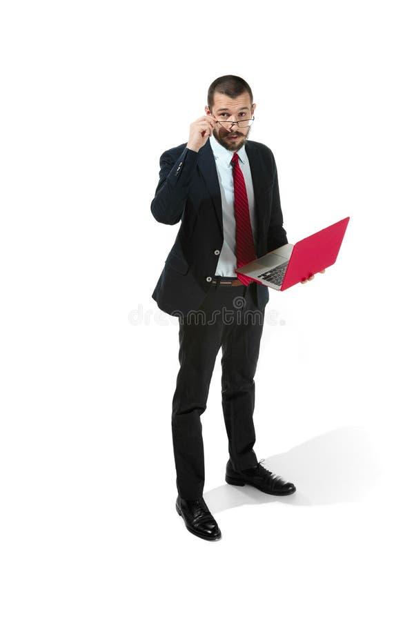 Imagem do homem farpado novo considerável que está sobre o fundo branco do estúdio com portátil fotografia de stock