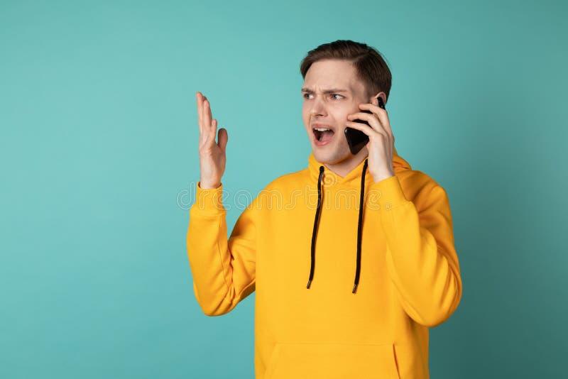 Imagem do homem gritando novo na posição do hoodie do yellowe isolado sobre o fundo azul da parede imagem de stock royalty free