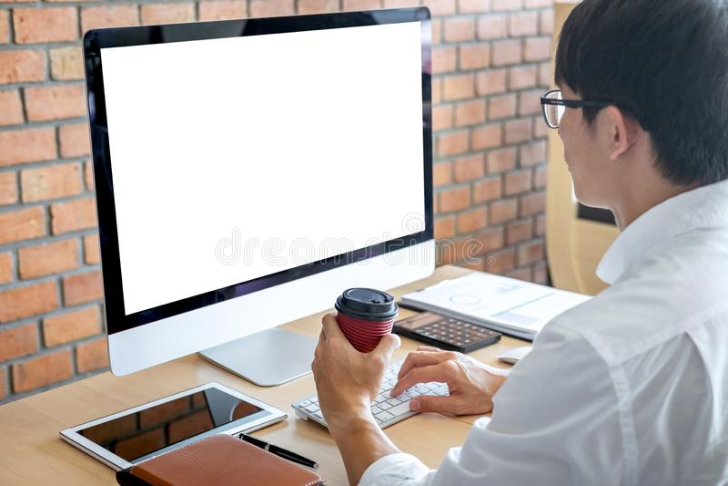 Imagem do homem novo que trabalha na frente do portátil do computador que olha a tela com uma tela branca limpa e o espaço vazio  foto de stock royalty free