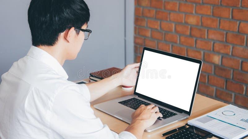 Imagem do homem novo que trabalha na frente do portátil que olha a tela com uma tela branca limpa e o espaço vazio para o texto e imagens de stock royalty free