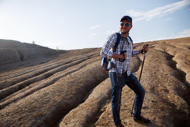 Imagem do homem novo do turista com bengalas que anda na área montanhosa foto de stock