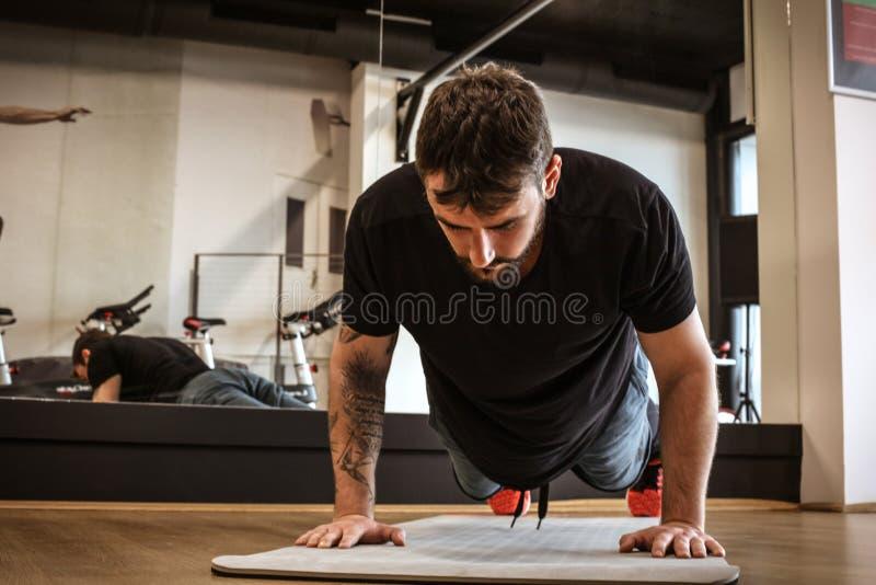 A imagem do homem que novo o funcionamento empurra levanta imagens de stock