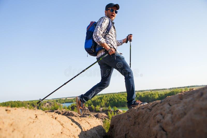 Imagem do homem do turista com bengalas que anda na área montanhosa imagens de stock