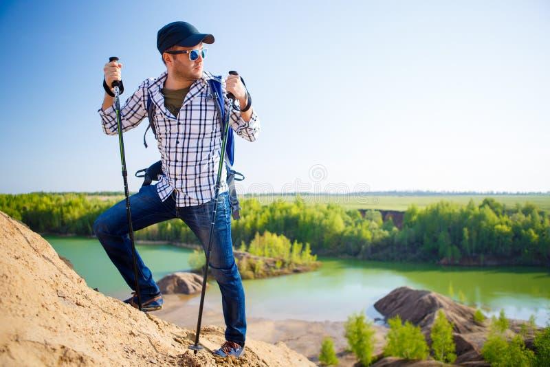 Imagem do homem do turista com a trouxa com as varas para andar no monte imagens de stock